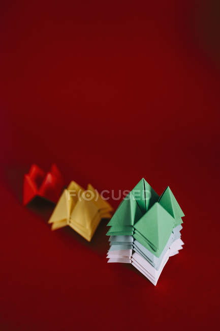 Multicolored origami fortune tellers on red background — Stock Photo