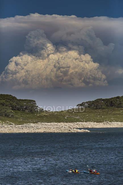 Байдарочники на воде с дымом, поднимающимся на заднем плане, водопад Крик, Виктория, Австралия — стоковое фото