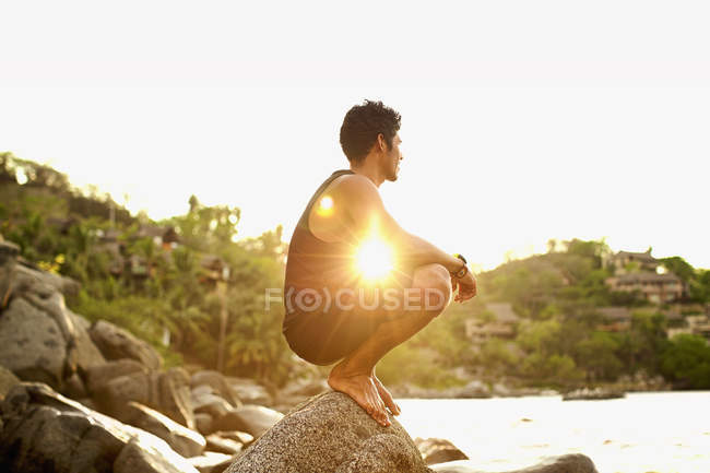 Serene young man crouching on ocean rock, Sayulita, Nayarit, Mexico — Stock Photo