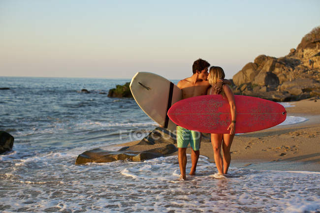 Young, affectionate couple with surfboards walking on sunny ocean beach, Sayulita, Nayarit, Mexico — Stock Photo