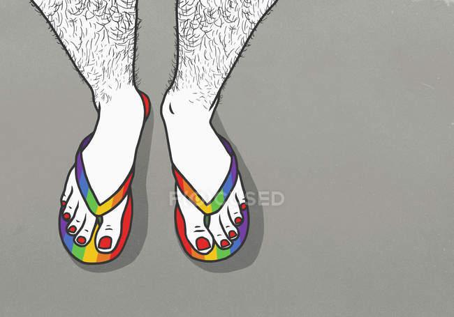 Hombre con piernas peludas y uñas de los pies pintadas con chanclas de arco iris - foto de stock