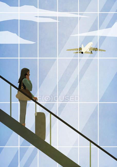 Ділова жінка з валізою на ескалаторі аеропорту — стокове фото