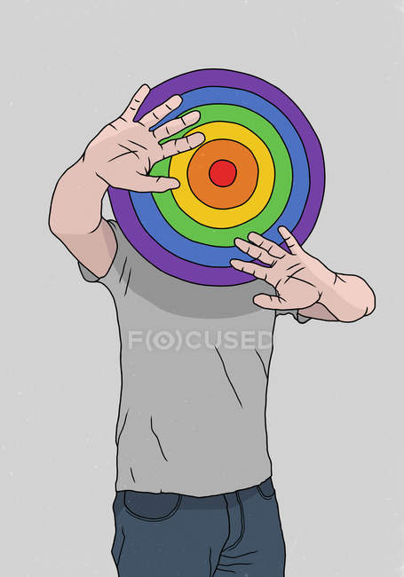 Man hiding behind rainbow dart board — Stock Photo