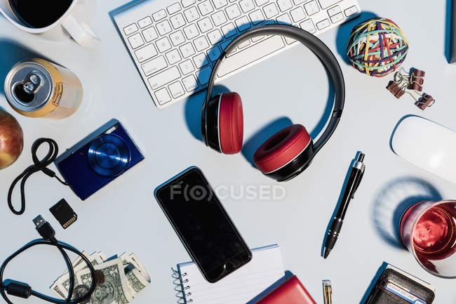 Вид сверху наушники, смартфон, цифровые фотоаппараты и канцелярские принадлежности на столе — стоковое фото
