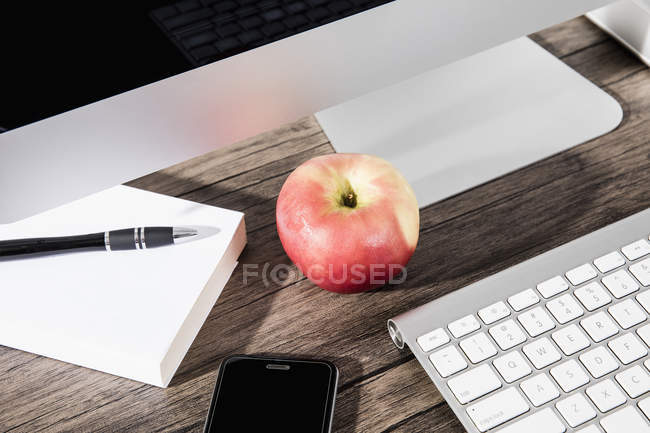 Apple и смартфон на столе под компьютером — стоковое фото