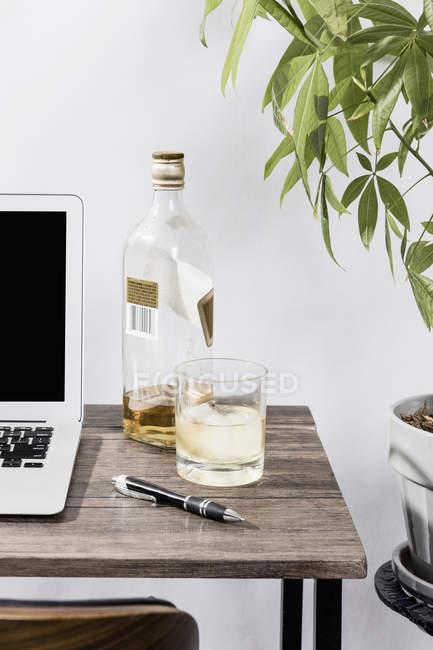 Whisky sur le bureau à côté de l'ordinateur portable dans le bureau — Photo de stock
