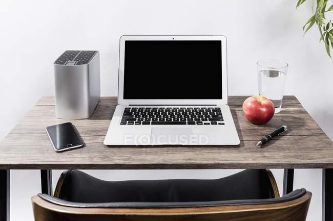 Computer portatile, smartphone, mela, acqua e penna sulla scrivania — Foto stock