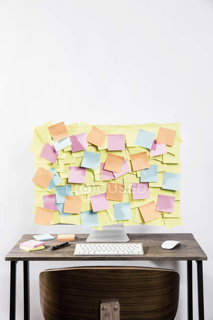 Adhesive notes covering computer in office — Stock Photo