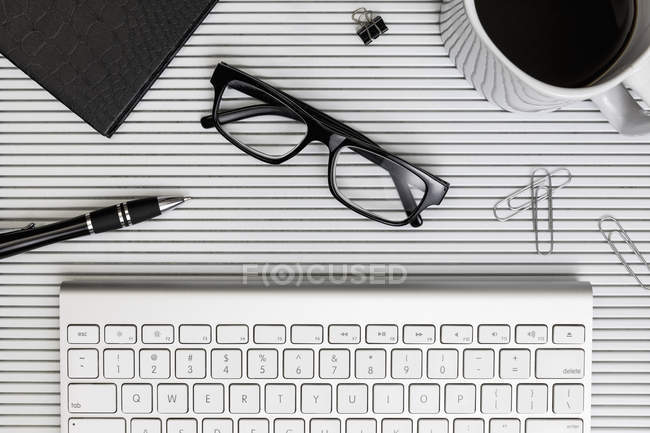 View form above eyeglasses, coffee, pen and paper clips on desk above computer keyboard — Stock Photo