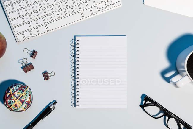 Veja o formulário acima do caderno em branco, alinhado na mesa abaixo do teclado de computador — Fotografia de Stock