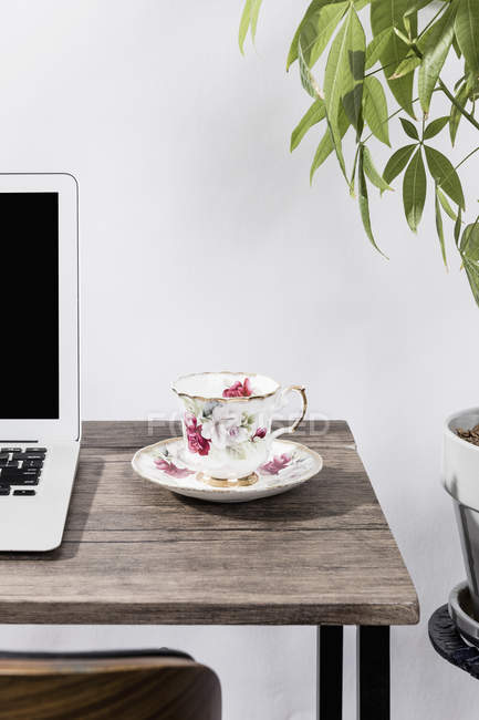 Tea cup on desk next to laptop in office — Stock Photo