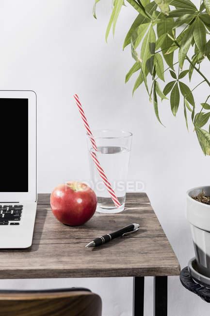 Wasser, Apfel und Stift auf dem Schreibtisch neben dem Laptop im Büro — Stockfoto