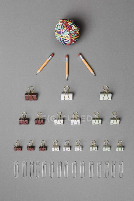 View form above rubber band ball, pencils, binder clips and paper clips on gray background — Stock Photo