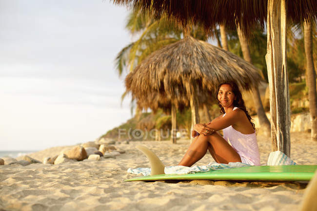 Portrait of confident female surfer with surfboard relaxing on sunny beach, Sayulita, Nayarit, Mexico — стокове фото