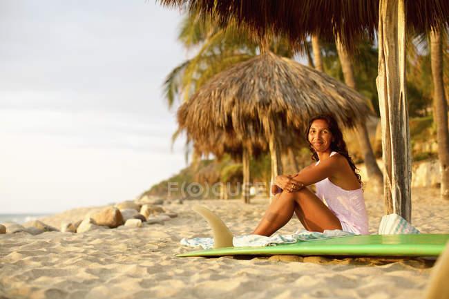 Ritratto di surfista fiduciosa con tavola da surf rilassante sulla spiaggia soleggiata, Sayulita, Nayarit, Messico — Foto stock