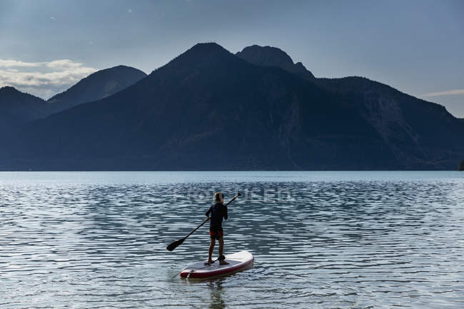 Boy paddle boarding on sunny, idilliaco lago di montagna, Walchensee, Baviera, Germania — Foto stock