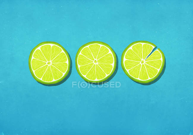 Vibrant green lime slices on blue background — Stock Photo