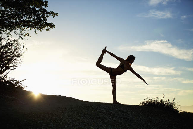 Silhouette of woman practicing king dancer yoga pose — Stock Photo