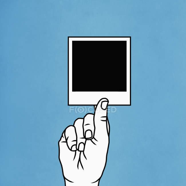 Рука тримає миттєву фотографію — стокове фото