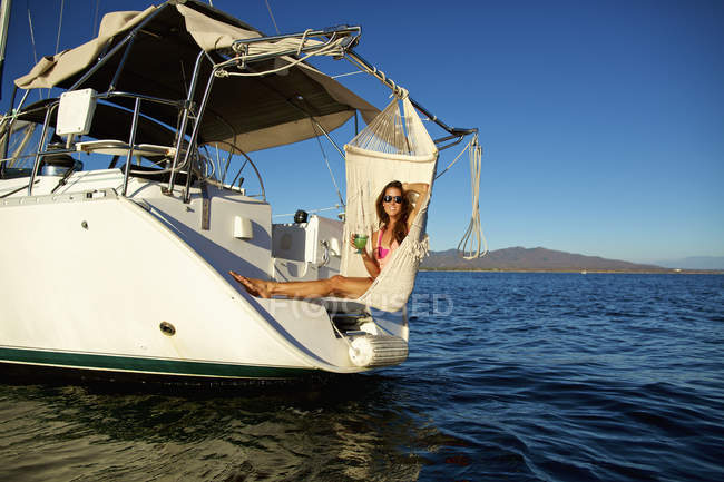 Portrait of carefree woman relaxing with cocktail in hammock on yacht over sunny ocean — Stock Photo