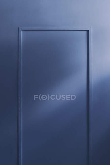 Сонячне світло над прихованими блакитними дверима — стокове фото