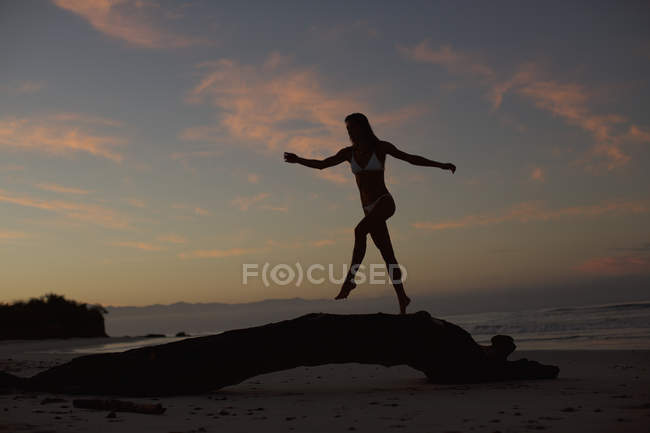 Silhouette of woman walking on driftwood on beach at dusk — стокове фото