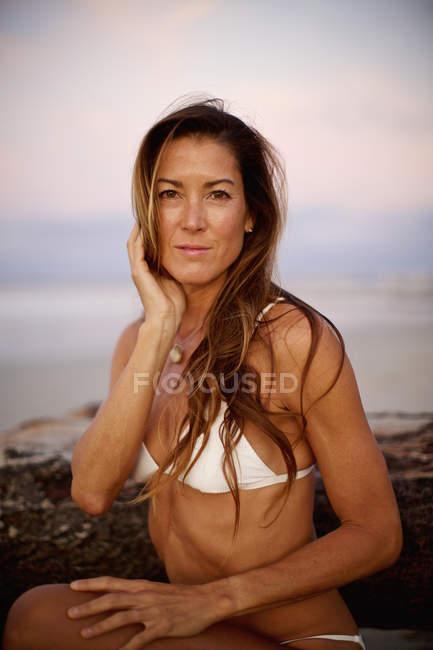 Portrait of confident woman in bikini on beach — стокове фото
