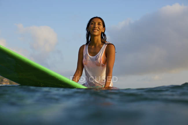 Smiling, confident female surfer waiting on surfboard in ocean — стокове фото
