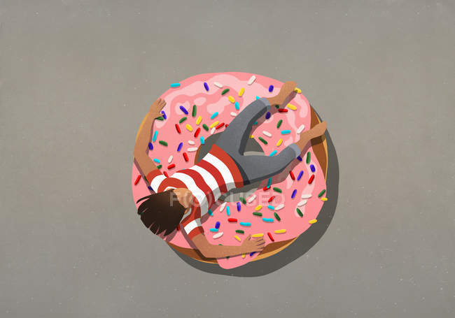 Girl relaxing on large donut with sprinkles — Stock Photo