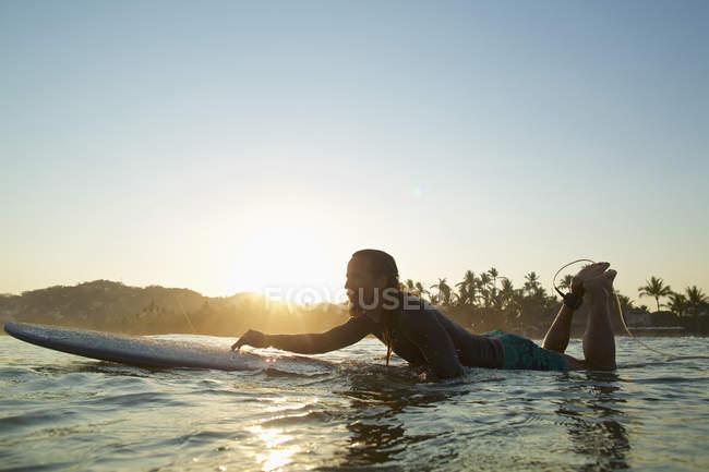 Männlicher Surfer, der auf dem Ozean bei Sonnenuntergang paddelt, sayulita, nayarit, Mexico — Stockfoto