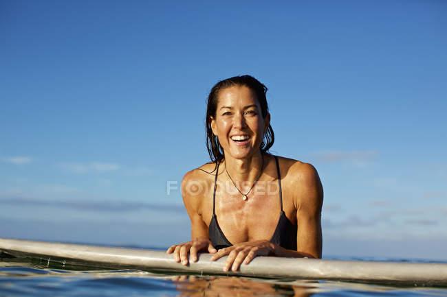 Портрет счастливой, уверенной женщины-серфера, опирающихся на доску для серфинга в океане — стоковое фото
