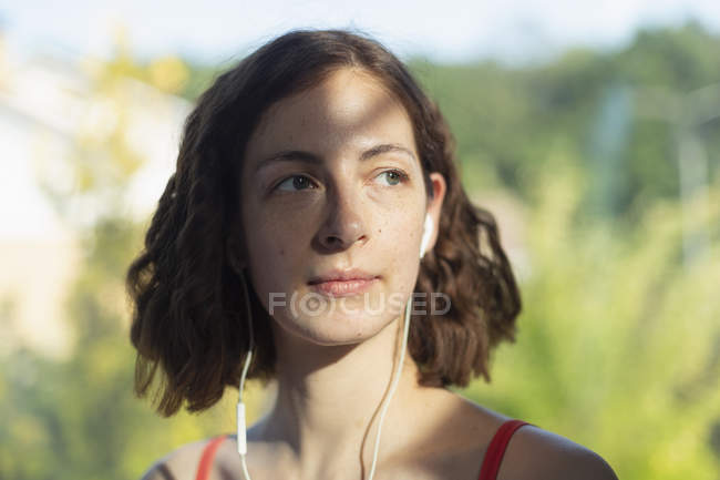 Thoughtful woman listening to music with headphones — Stock Photo