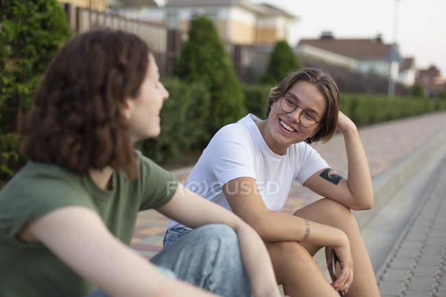 Women friends talking on neighborhood curb — Stock Photo