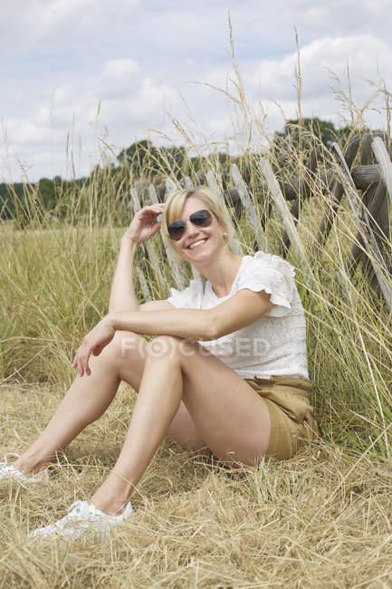 Портрет уверенной, беззаботной женщины, сидящей в высокой траве — стоковое фото
