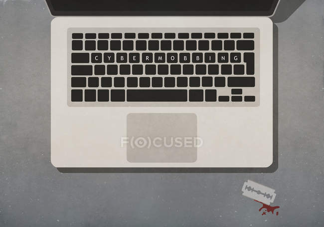Cyber Mobbing text on laptop keyboard next to razor blade with blood — Stock Photo