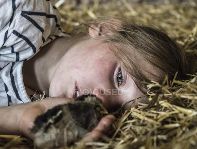 Gros plan sur une jeune fille tenant un petit poussin dans la paille — Photo de stock