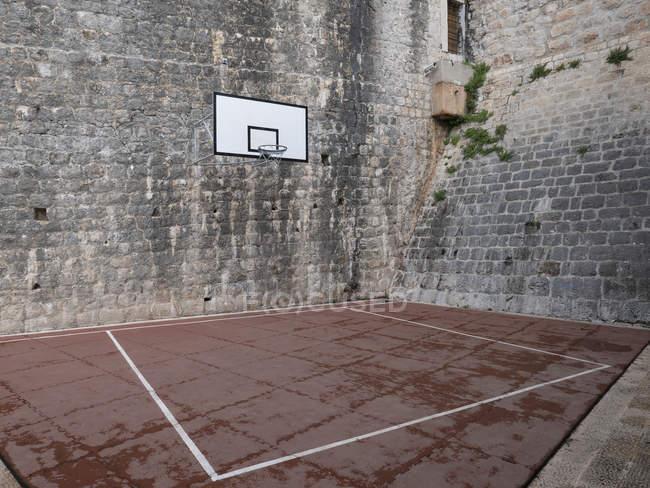 Баскетбольный корт и обруч в каменном дворе — стоковое фото