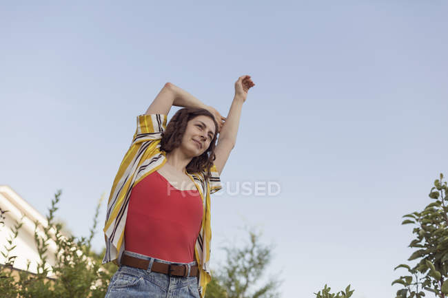 Carefree woman stretching arm overhead — Stock Photo
