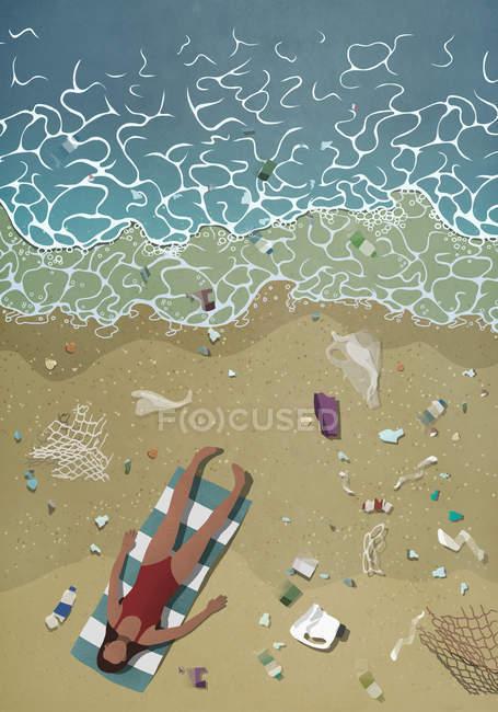 Мусор, окружающий женщину загорать на пляже океана — стоковое фото