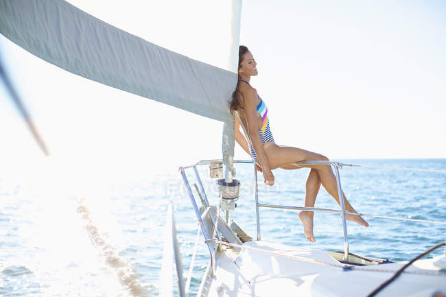 Carefree woman in bathing suit on sunny sailboat — Stock Photo