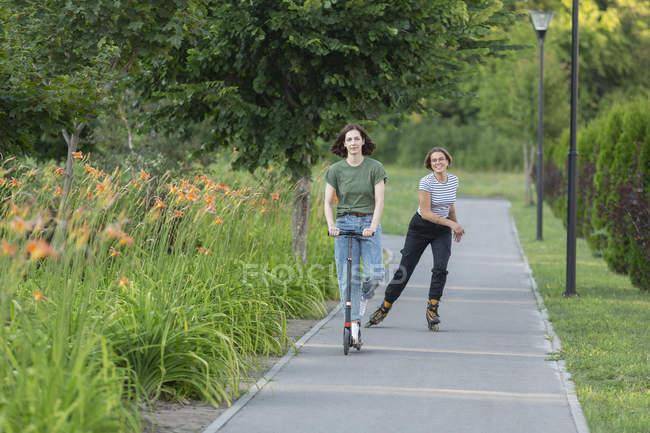 Femmes faisant du patin à roues alignées et de la trottinette sur le sentier du parc — Photo de stock