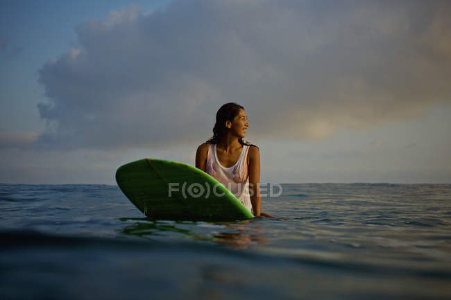 Female surfer waiting on surfboard in ocean — Stock Photo