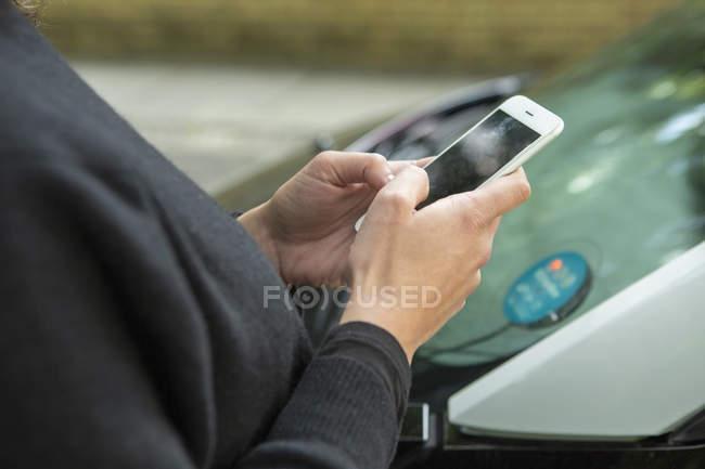 Закрыть женщину, использующую смартфон для доступа к автомобилю — стоковое фото