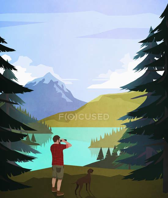 Man with dog using binoculars at scenic lakeside — Stockfoto