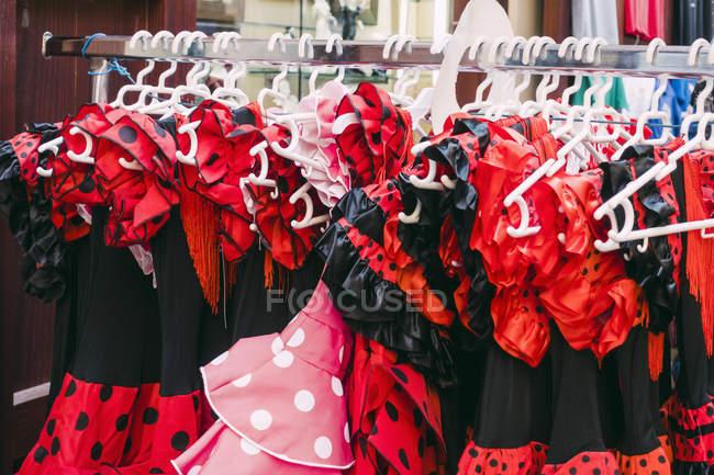 Abiti in costume a pois rossi e neri appesi al portabiti in negozio — Foto stock