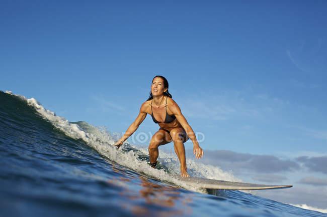 Female surfer riding ocean wave — Stock Photo