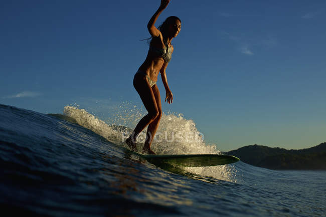 Female surfer riding ocean wave — Stock Photo