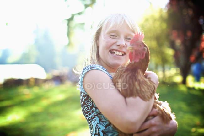 Porträt glückliches Mädchen hält Henne im sonnigen Hof — Stockfoto