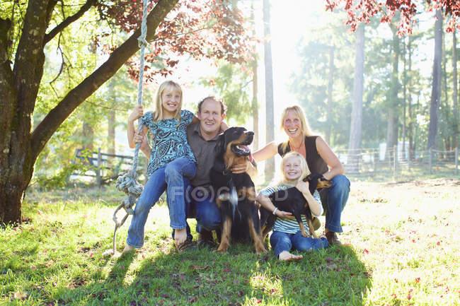 Retrato família feliz com cães no parque de outono ensolarado — Fotografia de Stock