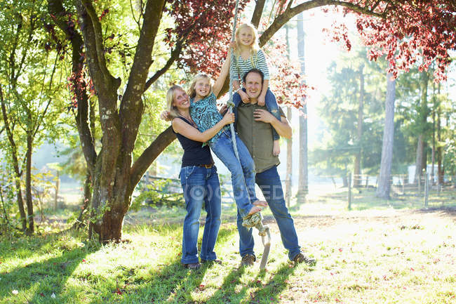 Portrait happy family on rope swing in sunny autumn park — Stock Photo